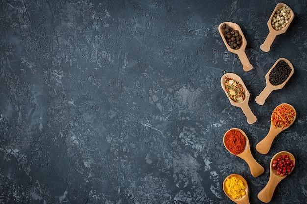 暗い石のテーブルに様々なスパイスのフレーム。カラフルなスパイス、上面図。有機食品、健康的なライフスタイル