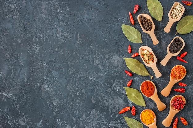 暗い石のテーブルに様々なスパイスのフレーム。カラフルなスパイス、上面図。有機食品、健康的なライフスタイル、テキスト用のスペース