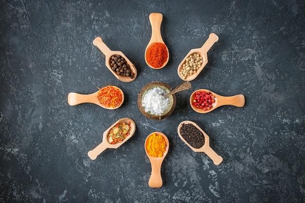 木のスプーン、種子、暗い石のテーブルの上のハーブの様々なインドのスパイス。カラフルなスパイス、上面図。有機食品、健康的なライフスタイル、テキスト用のスペース