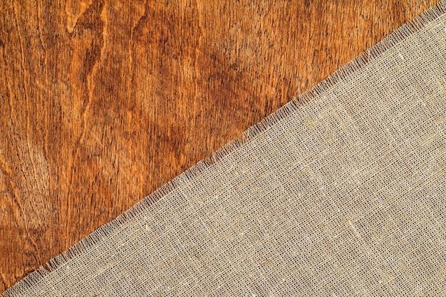 木製のテーブル表面に黄麻布の質感