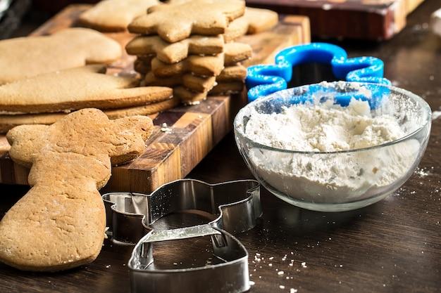 Делать рождественские печенья на деревянных фоне.