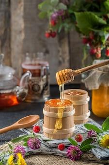 蜂蜜はスプーンから木製のボウルに滴ります