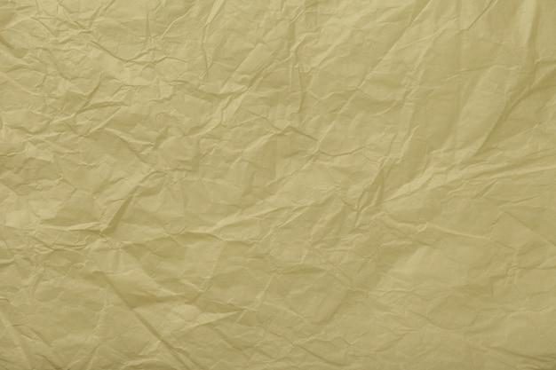 しわくちゃのベージュの包装紙、クローズアップのテクスチャ。黄金の古い背景