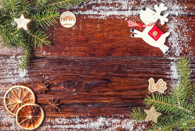 モミの枝、おもちゃの鹿、雪、オレンジで作られたクリスマスフレームは、木製の古い茶色の背景にレイアウトされています。