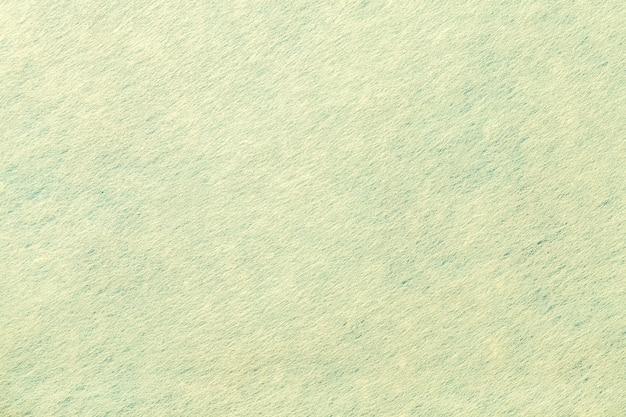 フェルト生地の明るい緑の背景。ウール織物のテクスチャ
