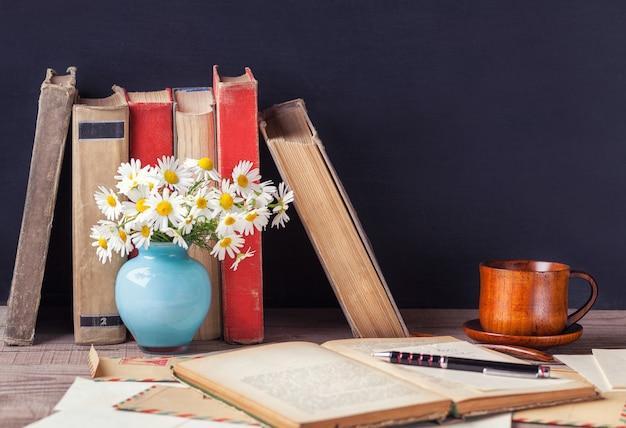 ビンテージ封筒の間で木製のテーブルの上に横たわる古い本を開く