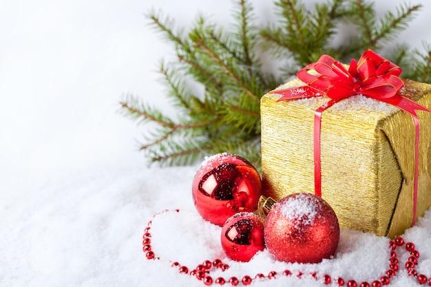 ゴールデンギフトと雪の上の赤いボールとクリスマスのコピースペースと白いグリーティングカード
