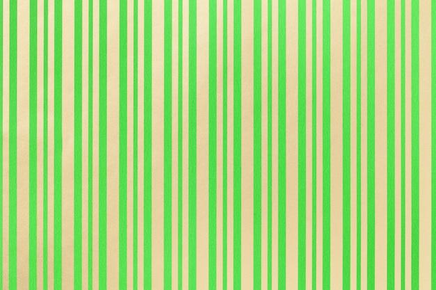 縞模様の紙の包装からの暗い緑と金色の背景、