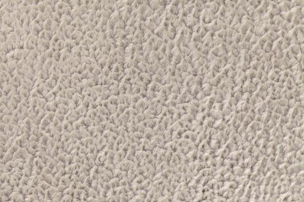 柔らかく、フリースの布のベージュ色の背景。繊維のクローズアップのテクスチャ