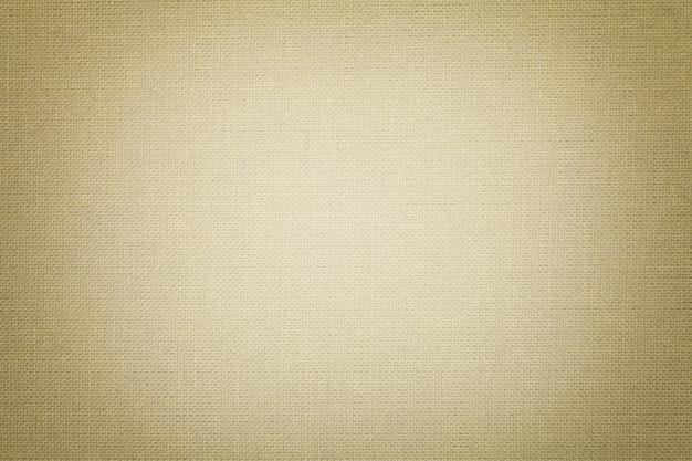 繊維材料からの明るいベージュの背景。自然な風合いの生地。背景。