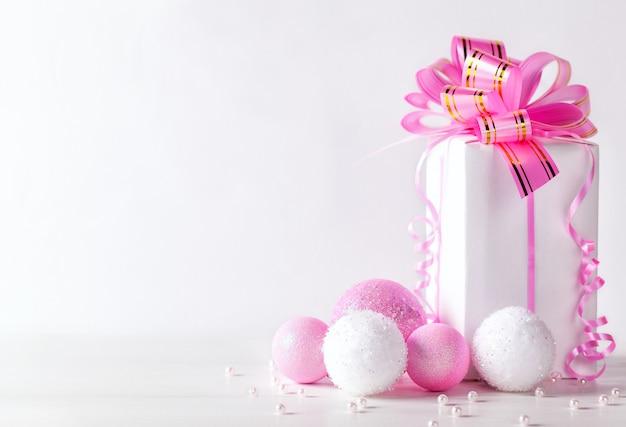 Белая открытка с копией пространства на рождество или новый год с упакованным подарком и розовым шаром