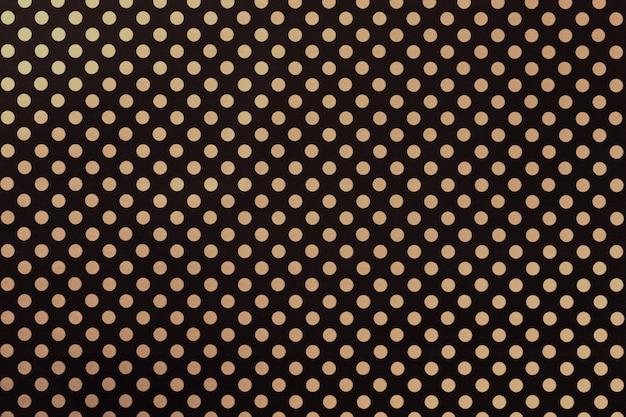 黄金の水玉のクローズアップのパターンを持つ包装紙から黒の背景。