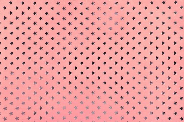 銀の星のパターンを持つ金属箔紙からピンクの背景