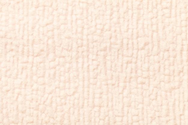 柔らかく、フリースの布の明るいベージュのふわふわの背景
