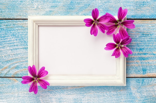 ピンクの紙の背景に紫の花を持つ白い木製フォトフレーム。