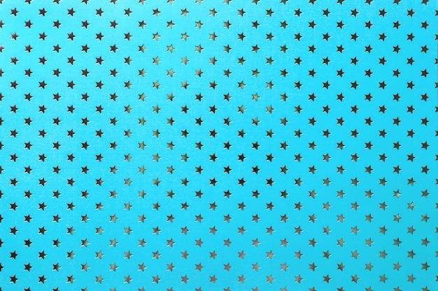 銀の星のパターンを持つ金属箔紙から青色の背景
