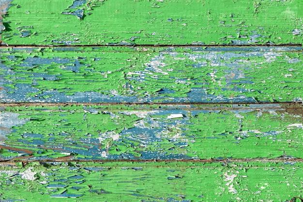 ひびの入った塗料で古い緑の木製の壁のテクスチャ。