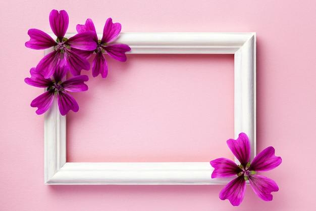 ピンクの紙の背景に紫の花と白い木製フォトフレーム