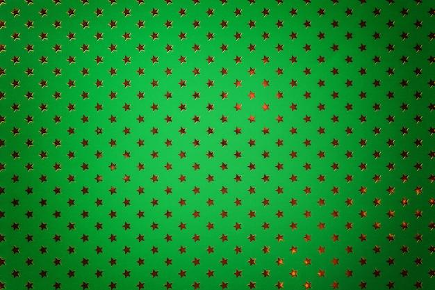金色の星を持つ金属箔紙から濃い緑色の背景