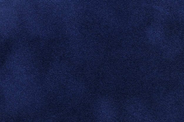 ダークブルーのスエード生地の背景。ネイビーブルーヌバックテキスタイルのベルベットマットテクスチャ