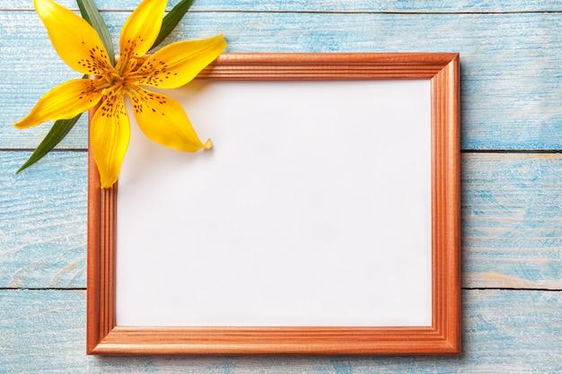 古い青いぼろぼろの背景に黄色の花ユリと茶色の木製フォトフレーム。