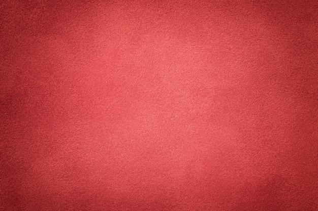 濃い赤のスエード生地のクローズアップの背景。ベルベットマットテクスチャ