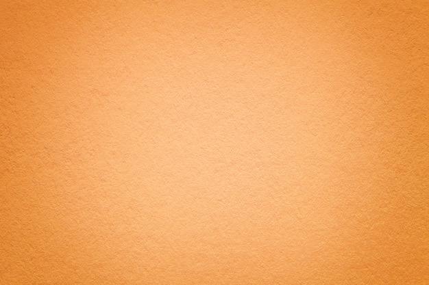 Текстура старой оранжевой бумажной предпосылки, крупного плана.