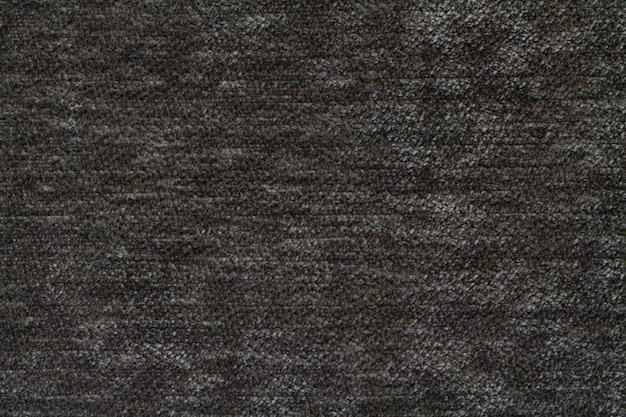 柔らかく、フリースの布の暗い灰色の背景。繊維のクローズアップのテクスチャ