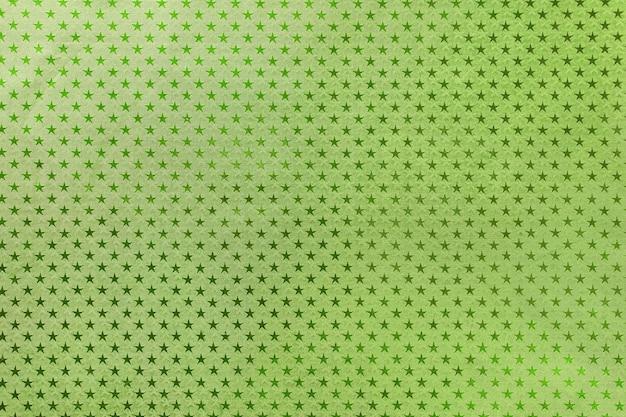 星のパターンを持つ金属箔紙から濃い緑色の背景