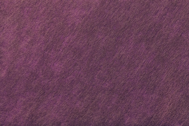 フェルト生地の暗い紫と茶色の背景。