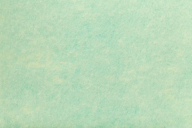フェルト生地の明るい青緑色の背景。