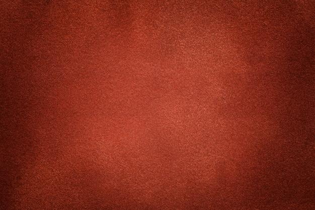暗いオレンジ色のスエード生地のクローズアップの背景。