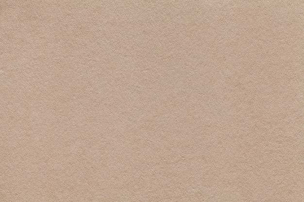古いベージュの紙のクローズアップのテクスチャ。高密度の段ボール砂色の構造。バックグラウンド。
