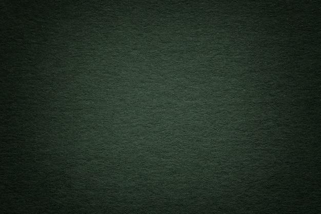 古い濃い緑色の紙の背景、クローズアップのテクスチャ。濃い青みがかった厚紙の構造。