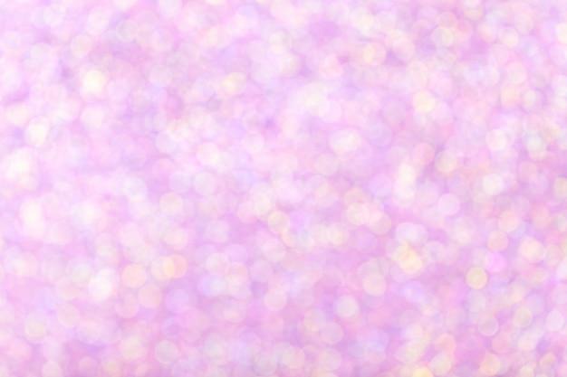 輝くライトとぼやけている光沢のあるピンクの背景