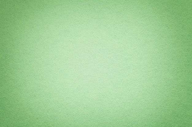 古い緑の紙の背景、クローズアップのテクスチャ。密な軽いオリーブのボール紙の構造。