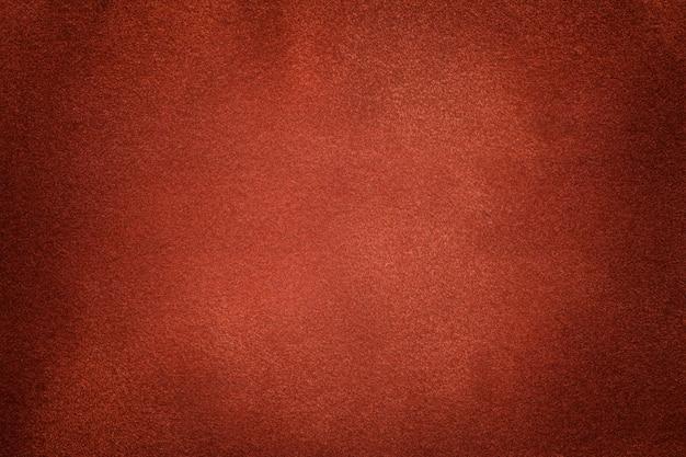 暗いオレンジ色のスエード生地のクローズアップの背景。ジンジャーヌバックテキスタイルのベルベットマットテクスチャ