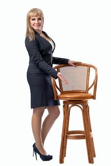 椅子に座るに誘う若い美しいビジネス女性。