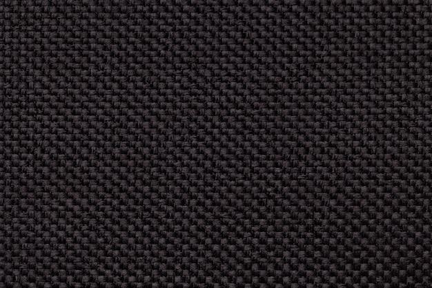 Черный фон с плетеной клетчатым узором, крупным планом. текстура плетения ткани, макро