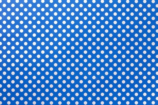 銀の水玉のクローズアップのパターンを持つ包装紙からネイビーブルーの背景