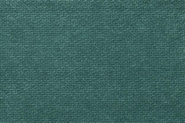 Темно-зеленый пушистый фон из мягкой, ворсистой ткани. текстура светлой пеленки ткани, крупным планом.