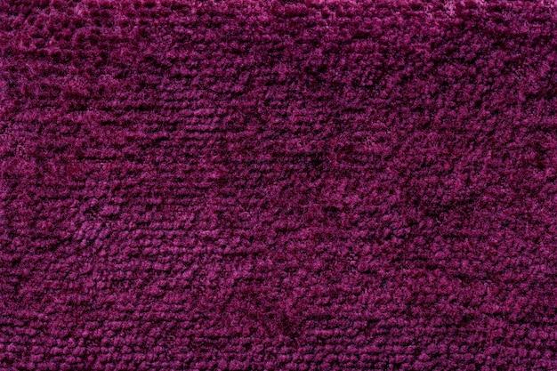 柔らかく、フリースの布の暗い紫色のふわふわの背景。繊維のクローズアップのテクスチャ
