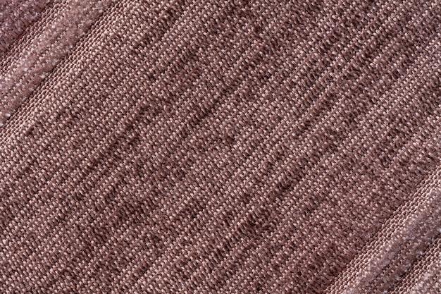 Коричневый фон из трикотажного текстильного материала. ткань с полосатой текстурой крупным планом.