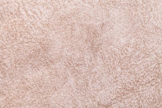 Светло-бежевый пушистый фон из мягкой, ворсистой ткани. текстура текстильной крупным планом.
