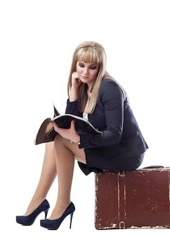 Молодая девушка, одетая в деловой костюм, сидит на чемодане и читает