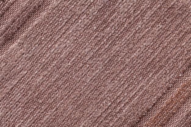 Светло коричневый фон из трикотажного текстильного материала. ткань с полосатой текстурой крупным планом.