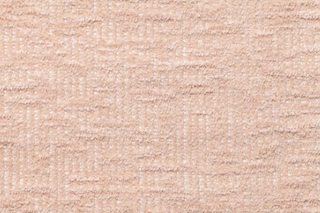 Светло-бежевый пушистый фон из мягкой, ворсистой ткани. текстура плюшевой меховой ткани, крупным планом.