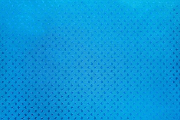 星のパターンを持つ金属箔紙から青色の背景