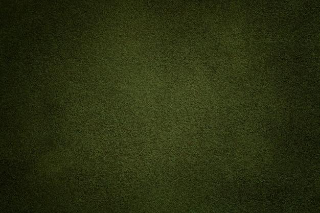 ダークグリーンのスエード生地のクローズアップの背景。オリーブヌバックテキスタイルのベルベットマットテクスチャ