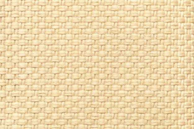 Светло-кремовый текстильный фон с клетчатым узором, крупным планом. структура ткани макроса.